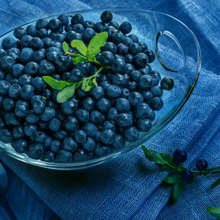 Freshly blueberries in glass bowl. Juicy and fresh blueberries with green leaves on blue wooden table. Blueberry antioxidant. Concept for healthy eating and nutrition. 2020 color classic blue Foto de archivo - 136104572