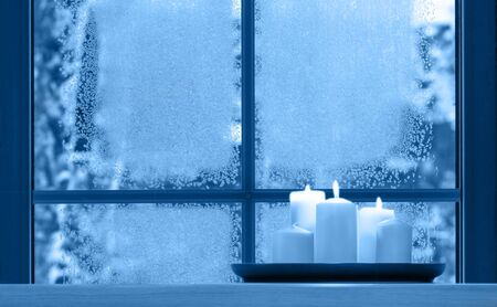 Beautiful burning candles and fairy lights on windowsill indoors