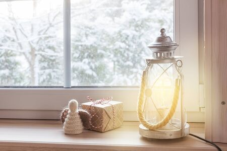 Festive Christmas lantern, gifts and angel on a wooden window sill in winter indoors. Christmas decoration, scandinavian style