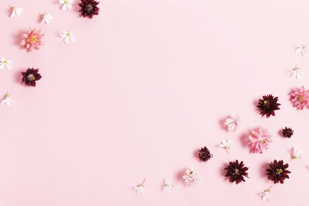 Festive flowers composition. Frame made of pink and purple small flowers on pink background.