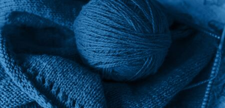 The process of knitting, woolen yarn of classic blue color on blue table. Banco de Imagens