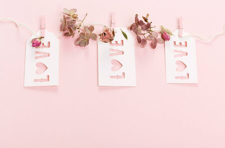vintage retro valentines day, wedding frames from pink dry roses flower with ribbon and inscription love. top view.