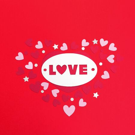 The word love is cut out on cardboard or paper on a red background with paper hearts.
