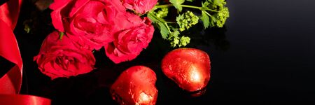 Red roses bouquet and heart-shaped chocolates, red ribbon on a black background Stock fotó