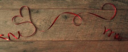 Heart shaped red ribbon on wood background , valentine background in vintage style