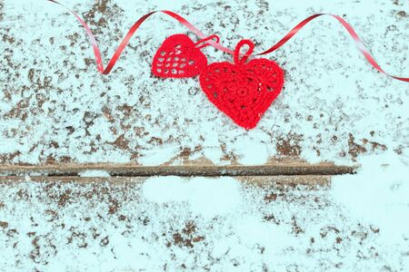 Crocheted red hearts with ribbon on snow. Valentines Day background.