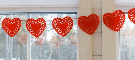 Home interior for Valentines day with window, hanging handmade hearts. Wedding, Valentines day concept