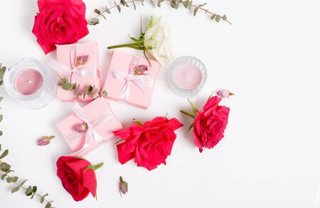 Festive flower red rose composition with pink gifts, frame. Overhead top view, flat lay. Copy space. Birthday, Mothers, Valentines, Womens, Wedding Day concept.