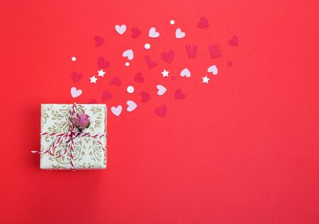 Gift with dry rose and the word love is cut out on cardboard or paper on a red background with paper hearts. Flat lay, top view. valentines day background Stock fotó
