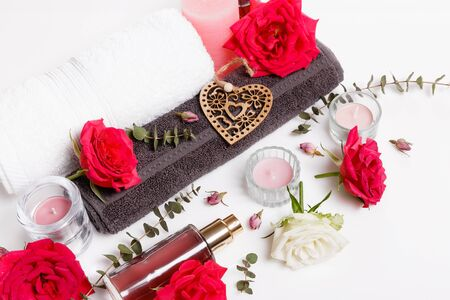 Spa concept in Valentines Day, red roses, candles, heart, towel, rose oil on white background
