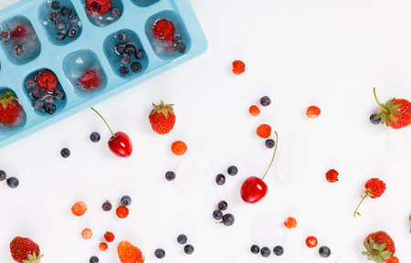 Fresh and frozen summer berries, strawberries, raspberries, blueberries, cherries on a white background