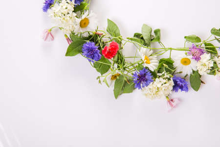 Wreath of wildflowers bindweed, chamomile, cornflower, poppy isolated on a white background.