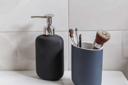 Bathroom interior with liquid soap bottle and makeup brushes closeup. Modern bathroom design