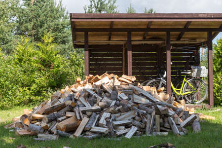 Firewood harvested for heating in winter. A pile of firewood in the courtyard of the house on the green grass