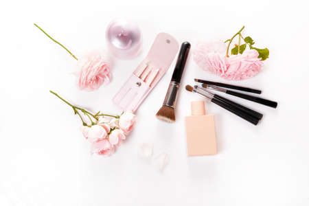 Brush, cosmetic and pink rose on a white background