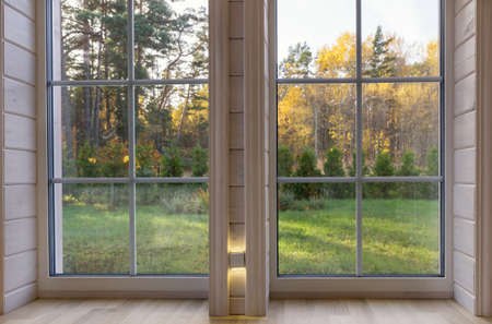 Bright interior of the room in wooden house with a large window overlooking the autumn courtyard. Zdjęcie Seryjne