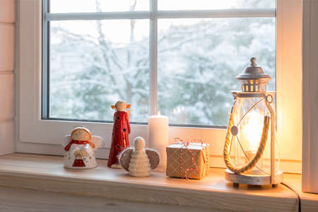 Christmas lantern, angels with gifts on the window of a wooden house overlooking the winter garden at night in winter.