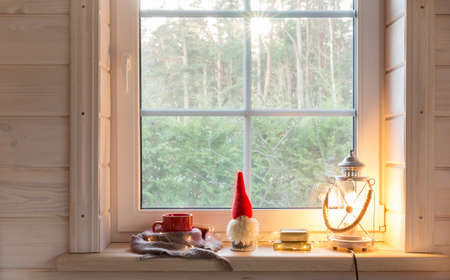 Christmas lantern, Christmas gnome,and red mug on the window of a wooden house overlooking the winter garden.