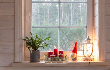 Christmas lantern, Angel, Christmas gnome, Christmas Cactus and red mug on the window of a wooden house overlooking the winter garden.