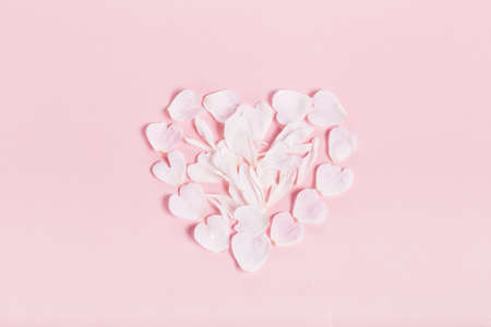 Pink rose petals in a heart shape on pink background. Flat lay, top view 写真素材