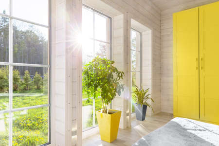 Bright interior, room in wooden house with large window. Scandinavian style. The trendy colors of 2021 are gray and yellow