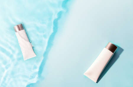 Tube of sunscreen on blue water surface. Cosmetic cream lotion, sunscreen on blue background of summer pool. Summer vacation cosmetics concept.