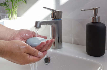Man use soap and washing hands under the water tap .Hygiene concept. Washing hands with soap 写真素材