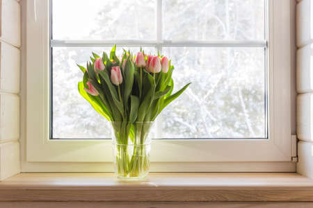 Bouquet of beautiful pink tulips on a wooden windowsill. White window in a Scandinavian style wooden house overlooking the garden, pine forest. Spring concept, Happy 8 March, Womens Day