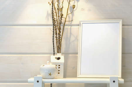 Wooden white wall in a scandinavian house, mockup of a white photo frame on a shelf, dry flowers.