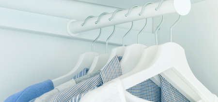 White wardrobe with light blue shirts and blouses hanging on hangers. 免版税图像 - 165731564