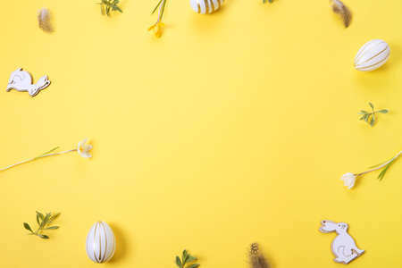 Festive Easter border, frame from easter eggs and spring flower crocus on yellow background. Stylish easter flat lay yellow, great design for any purposes.