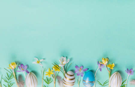 Festive Easter border, frame from easter eggs and spring flower crocus on blue background. Stylish easter flat lay blue,