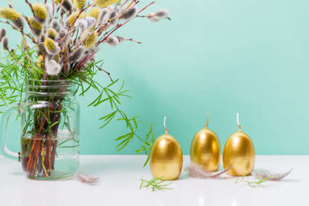 Easter decoration with eggs and golden candles and ribbons on blue background