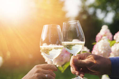 Couple romantically celebrate outdoors with glasses of white wine, proclaim toast People having dinner in a home garden in summer sunlight. Foto de archivo