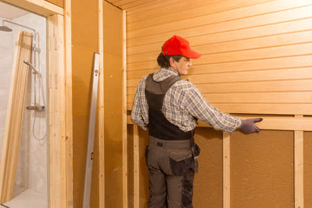 Sauna construction, finishing. The man is screwing a wooden bench to the wall.