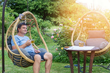 Man resting in rattan cocoon wicker chair with cup of tea near blooming roses in backyard in summer
