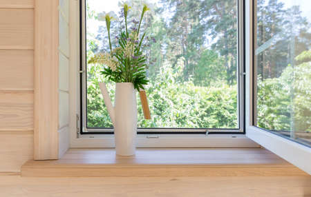 White window with mosquito net in a rustic wooden house overlooking the garden. Bouquet of white irises and lupins in watering can on the windowsill