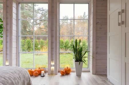 Bright photo studio interior with big window, high ceiling, white wooden floor, autumn, fall concept 免版税图像