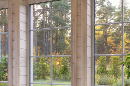Bright interior of the room in wooden house with a large window overlooking the autumn courtyard. Golden autumn landscape in white window.