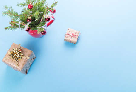 Christmas composition, gifts and christmas tree in a red mug on a blue background 免版税图像