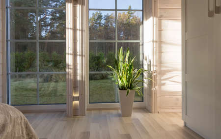 Bright interior of the room in wooden house with a large window overlooking the autumn courtyard. Home and garden, fall concept.