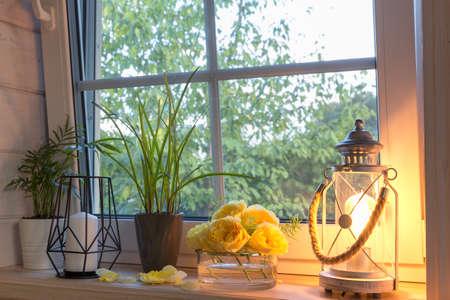 Yellow roses on windowsill, candles, autumn leaves, lantern. 免版税图像
