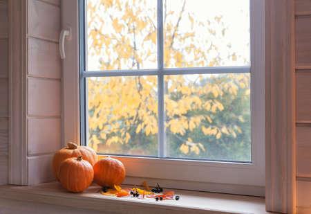 Orange pumpkins on windowsill, candles, autumn leaves, lantern. 免版税图像