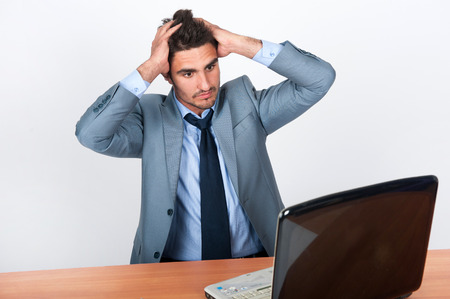 solves: The businessman in a gray suit and tie at work holding head with his hands and solves the problem Stock Photo