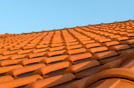 suffusion: Red tile roof closeup on blue sky background Stock Photo