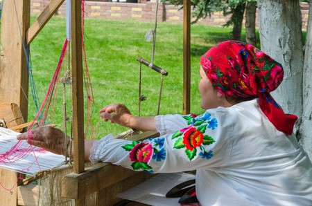 craftswoman: GOMEL, BELARUS - MAY 22, 2015: Outdoor event City of Masters. Belorussian craftswoman works at the old loom