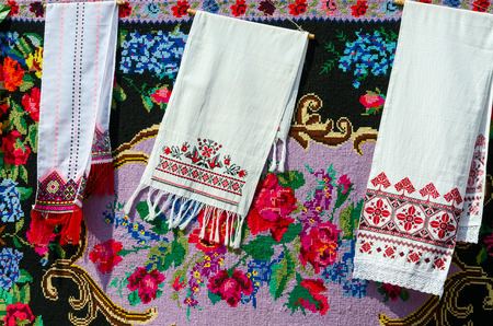 bedcover: Belorussian towels with vintage ornament on the background of rustic homespun carpet with bright floral pattern Stock Photo