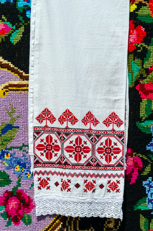 bedcover: Belorussian embroidered towel with traditional ornaments on background rustic homespun carpet with bright floral pattern Stock Photo