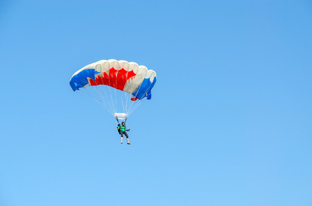 is cloudless: ZYABROVKA, BELARUS - AUGUST 8, 2015: Unknown woman -  skydiver performs a jump on the background of a cloudless blue sky