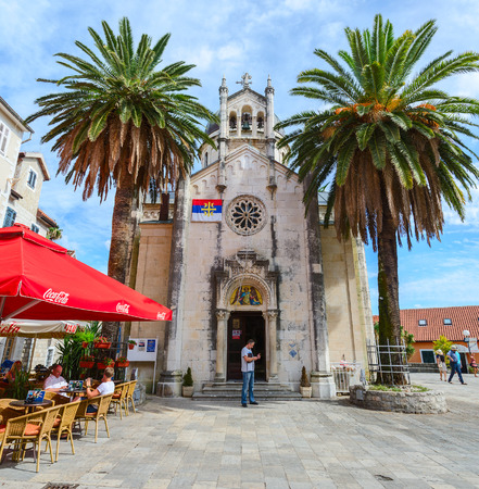 archangel: HERCEG NOVI, MONTENEGRO - SEPTEMBER 25, 2015: Unidentified tourists walk on the square Duke Stefan (Bellavista) near Orthodox Church of Archangel Michael in Herceg Novi, Montenegro